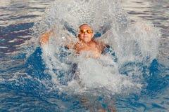 Junger hübscher blonder Mann in der Sonnenbrille taucht im Pool in Stockfoto