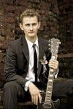 Junger hübscher Bräutigam, der eine Gitarre, Weinlese, Schwarzweiss-Foto sitzt und hält stockbild