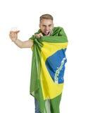 Junger hübscher Brasilien-Anhänger, der das Bier zujubelt mit Brasilien-Flagge hält Stockfotografie