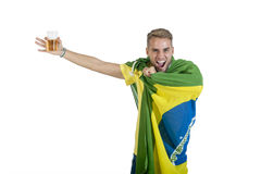 Junger hübscher Brasilien-Anhänger, der das Bier zujubelt mit Brasilien-Flagge hält Lizenzfreie Stockbilder