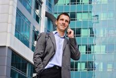 Junger hübscher, erfolgreicher Geschäftsmann, der am Telefon in der Stadt, vor modernem Gebäude spricht Lizenzfreies Stockbild