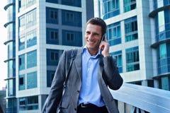 Junger hübscher, erfolgreicher Geschäftsmann, der am Telefon in der Stadt, vor modernem Gebäude spricht Stockbilder