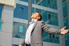 Junger hübscher, erfolgreicher Geschäftsmann, der am Telefon in der Stadt, vor modernem Gebäude spricht Sieger, Erfolg und Freihe Lizenzfreie Stockfotografie