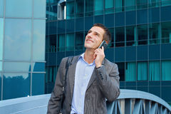 Junger hübscher, erfolgreicher Geschäftsmann, Manager, der am Telefon in der Stadt, vor modernem Gebäude spricht Lizenzfreie Stockfotografie