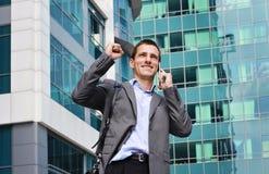 Junger hübscher, erfolgreicher Geschäftsmann, Manager, der am Telefon in der Stadt, vor modernem Gebäude spricht Führer und Siege Stockfoto