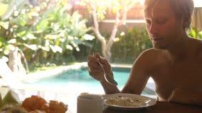 Junger hübscher Fleisch fressender Haferbrei frühstückt im Urlaub sitzend auf seinem Landhaus auf Swimmingpool auf dem Hintergrun lizenzfreie stockfotos