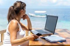 Junger hübscher Frauenfreiberuflerverfasser, der mit Laptopnotizblock und Telefon vor blauem tropischem Meer arbeitet Lizenzfreie Stockbilder