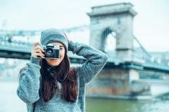 Junger hübscher Frauenphotograph, der alte Brücke auf Hintergrund schießt Lizenzfreie Stockbilder