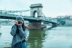 Junger hübscher Frauenphotograph, der alte Brücke auf Hintergrund schießt Stockfoto