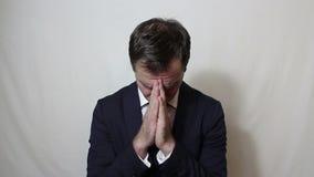 Junger hübscher Geschäftsmann betet und bittet Gott um Hilfe im Geschäft stock video