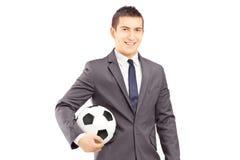 Junger hübscher Geschäftsmann, der einen Fußball hält Lizenzfreie Stockbilder