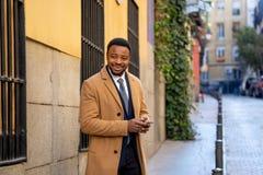 Junger hübscher Geschäftsmann, der Handy App sendet Mitteilung außerhalb des Büros in der städtischen Stadt verwendet stockbild