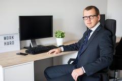 Junger hübscher Geschäftsmann, der im modernen Büro sitzt stockbild