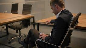 Junger hübscher Geschäftsmann, der seinen Smartphone, sitzend auf Stuhl im Büro betrachtet stock footage
