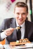 Junger hübscher Geschäftsmann, der Sushi mit Stöcken isst stockfotos