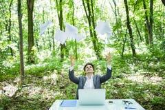 Junger hübscher Geschäftsmann im Arbeitstabellenbüro mit Laptop im grünen Wald mit Fliege tapeziert leere Unkosten Die goldene Ta lizenzfreies stockfoto
