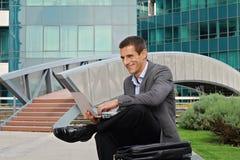 Junger hübscher Geschäftsmann, Manager, der draußen Laptop in der Stadt, vor modernem Gebäude verwendet Stockfotografie