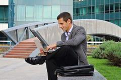 Junger hübscher Geschäftsmann, Manager, der draußen Laptop in der Stadt, vor modernem Gebäude verwendet Stockfoto