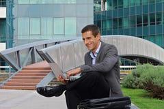Junger hübscher Geschäftsmann, Manager, der draußen Laptop in der Stadt, vor modernem Gebäude verwendet Lizenzfreie Stockfotos