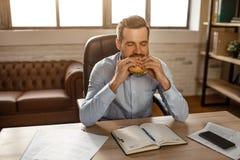 Junger hübscher Geschäftsmann sitzen bei Tisch und schneidender Burger in seinem eigenen Büro Er hat Mittagspause Hungriger junge stockfotografie