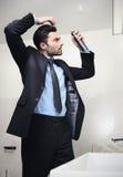 Junger hübscher Geschäftsmann stellt Haar her Stockfoto