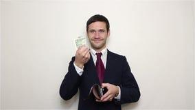Junger hübscher Geschäftsmann sucht nach Geld in seiner Geldbörse und findet einen Dollar stock video footage