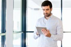 Junger hübscher Geschäftsmann unter Verwendung seiner Berührungsfläche, die im Büro steht lizenzfreie stockfotografie
