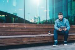 Junger hübscher Hippie-Mann sitzt auf, trinkendem Kaffee der Holzbank im Freien und hört Musik auf seinem Smartphone Lizenzfreie Stockfotografie
