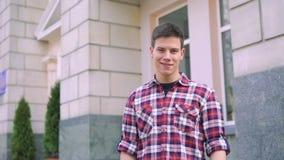 Junger hübscher Junge, der seine Uhr, stehend auf dem Gebäudehintergrund betrachtet stock video footage