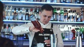 Junger hübscher Kellner im mischenden Alkoholinnencocktail der Bar Stockbilder