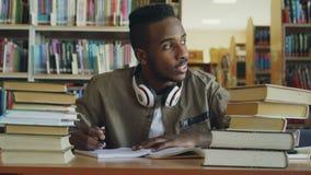 Junger hübscher Kerl des positiven Afroamerikaners mit großen Kopfhörern sitzt bei Tisch mit den Büchern und schaut durch Fenster stock video