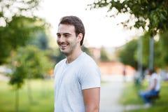 Junger hübscher Kerl im Parkstandign und -c$lächeln stockfoto