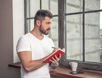 Junger hübscher Kerl steht das Fenster mit einer Schale bereit, zu gehen der Kaffee, hält Blockanmerkung in seiner Hand und macht lizenzfreie stockfotos