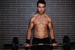 Junger hübscher Kerl Weightlifter anhebender Barbell, der Kasten ausüben und Bizepse mischen an der Turnhalle mit Lizenzfreie Stockbilder