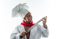 Junger hübscher Koch auf einem weißen Hintergrund in einer großen Kappe Stockfoto