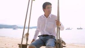 Junger hübscher lächelnder Geschäftsmann, der auf Hängematte auf exotischem Strand schwingt lizenzfreies stockbild