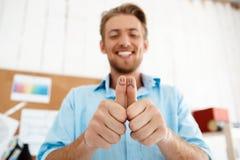 Junger hübscher lächelnder Geschäftsmann, der sich Daumen mit lustigen Gesichtszeichnungen zeigt Fokus auf Händen Weißes modernes Stockfoto