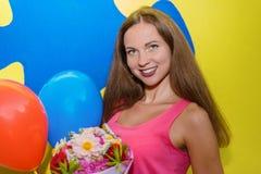 Junger hübscher Mädchen Brunette, der einen Blumenstrauß des Flusses lächelt und hält stockbilder