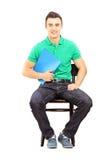 Junger hübscher Mann, der auf einem StuhlwarteVorstellungsgespräch sitzt Stockfotografie