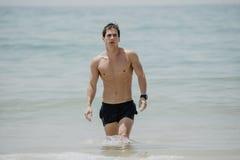 Junger hübscher muskulöser Mann, der aus dem Wasser in einem tropischen Strand heraus trägt einen Badeanzug geht lizenzfreie stockfotos