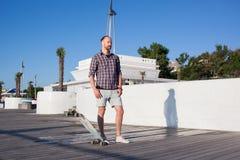 junger hübscher Schlittschuhläufer, der auf dem Sommerstrand aufwirft Lizenzfreie Stockfotografie