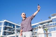 junger hübscher Schlittschuhläufer machen selfie nahe dem Hotel Lizenzfreies Stockfoto