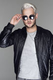 Junger hübscher sexy bärtiger Mann in der Lederjacke und in der Sonnenbrille Stockbild