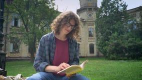 Junger hübscher Student in den Gläsern mit Buch des gelockten Haares Leseund Betrachten der Kamera, sitzend im Park nahe Universi stock video footage