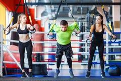 Junger hübscher Trainer mit junger und sportlicher Frau in der Turnhalle Getrennt auf Weiß stockfoto
