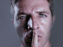 Junger hübscher und attraktiver Mann mit dem Finger auf seinem geschlossenen Mund, der, um oben zu schließen und warnt nicht in d stockbild