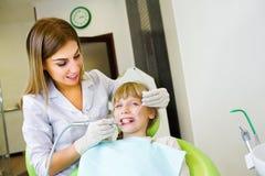 Junger hübscher Zahnarzt behandelt Zahnkind, einen Frauenzahnarzt stockfotografie