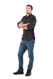 Junger hübscher zufälliger Mann in den Jeans und im Hemd mit den gekreuzten Armen, die oben schauen Stockfoto