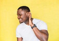 Junger h?bscher Afroamerikanermann, der versucht, besseres durch die Befestigung seiner Palme zum Ohr zu h?ren stockfotografie