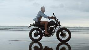 Junger h?bscher Hippie-Mann, der modernen kundenspezifischen Motorradrennl?ufer auf den schwarzen Sandstrand nahe dem Wasser reit stock video